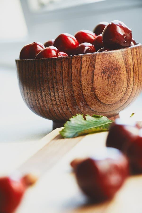 Bagas da cereja na bacia de madeira imagens de stock royalty free