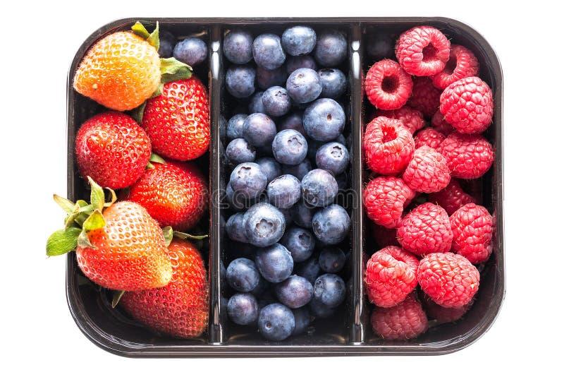 Bagas deliciosas Mirtilos, morangos e framboesas em uma caixa isolada no fundo branco Vista superior Alimento saudável do verão imagem de stock