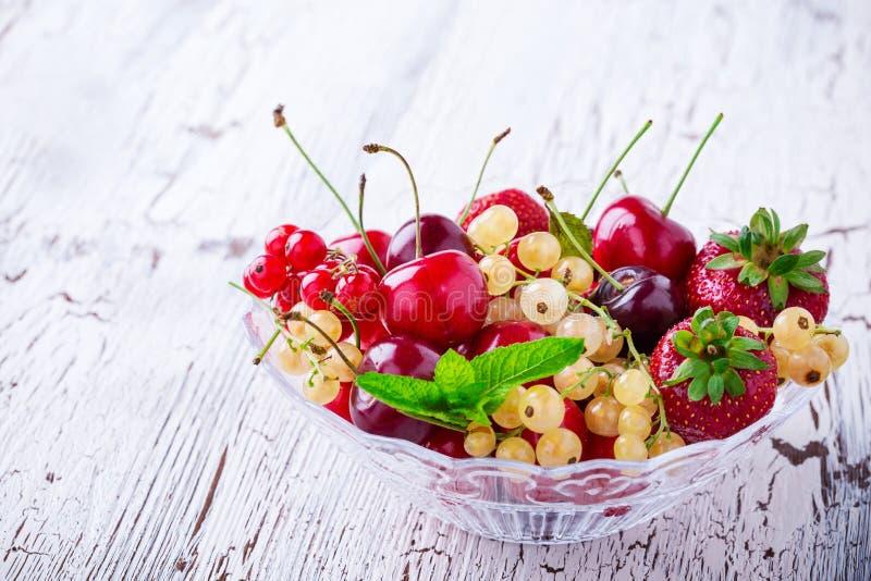 Bagas e frutos frescos do verão na bacia de vidro imagens de stock