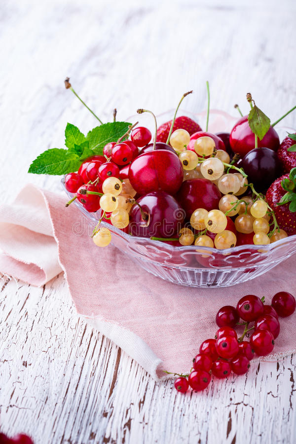 Bagas e frutos frescos do verão na bacia de vidro fotografia de stock royalty free