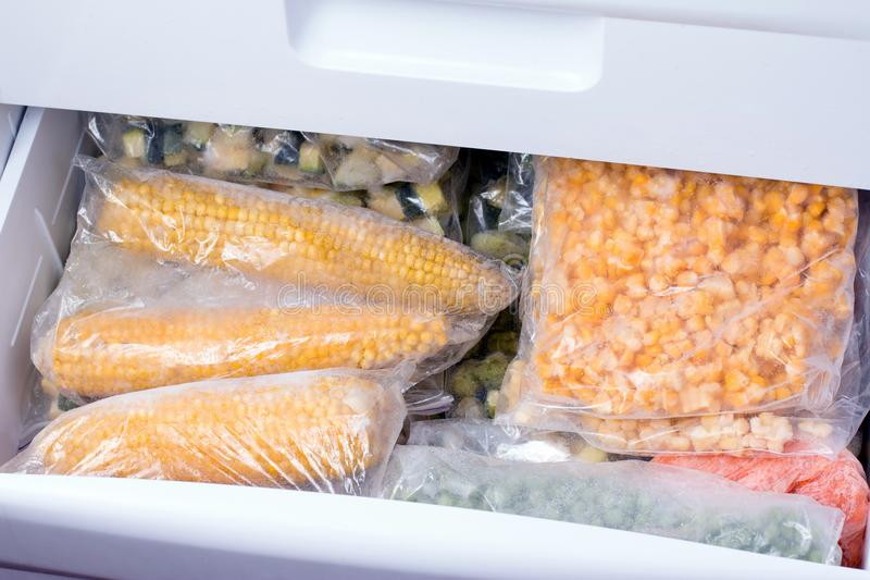 Bagas e vegetais congelados nos sacos no congelador, fim acima fotografia de stock