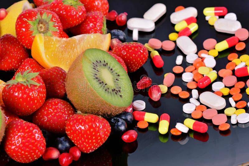 Bagas, frutos, vitaminas e suplementos nutritivos foto de stock