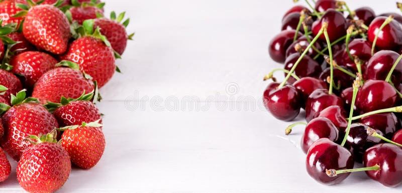 Bagas maduras bonitas frescas em morangos doces e em Cherry Frame Long de um fundo de madeira branco fotos de stock