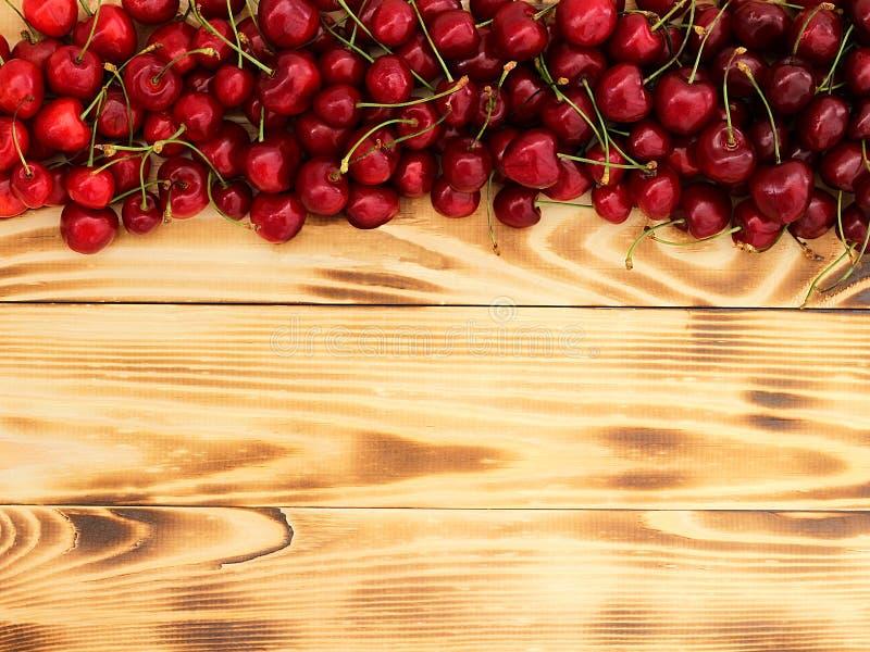 Bagas maduras da cereja em uma bandeja de madeira fotografia de stock