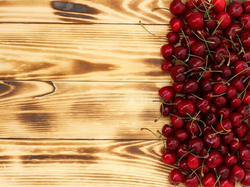 Bagas maduras frescas da cereja em uma bandeja de madeira ?rea de texto imagens de stock royalty free