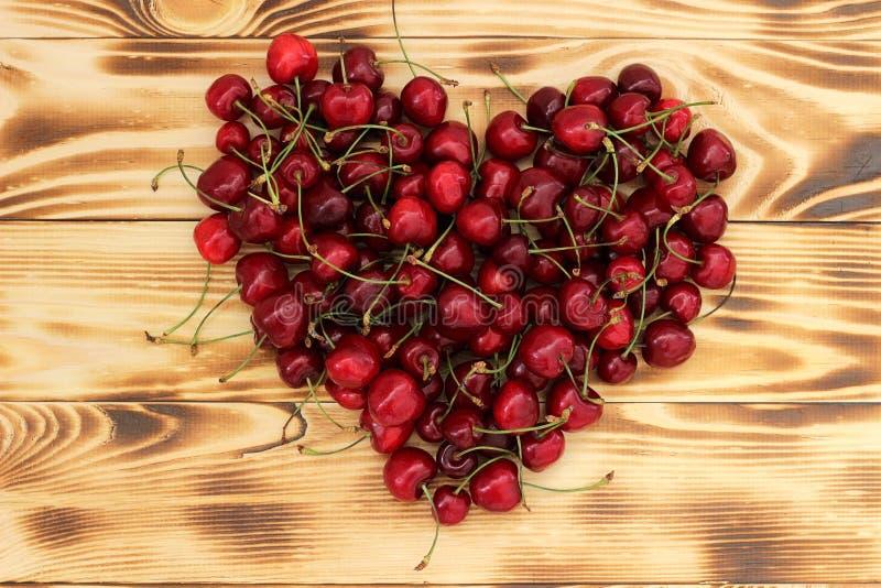 Bagas naturais maduras da cereja em uma bandeja de madeira na forma de um coração imagem de stock