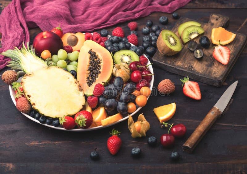 Bagas orgânicas cruas frescas do verão e frutos exóticos na placa branca no fundo de madeira escuro com placa e faca de desbastam fotos de stock royalty free