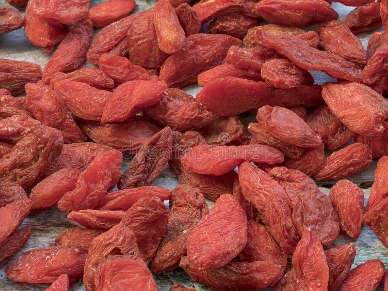 Bagas secadas vermelhas do goji Bagas de Goji no fundo de madeira foto de stock