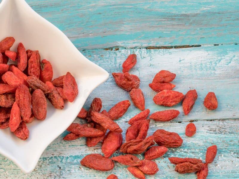 Bagas secadas vermelhas do goji Bagas de Goji no fundo de madeira fotografia de stock