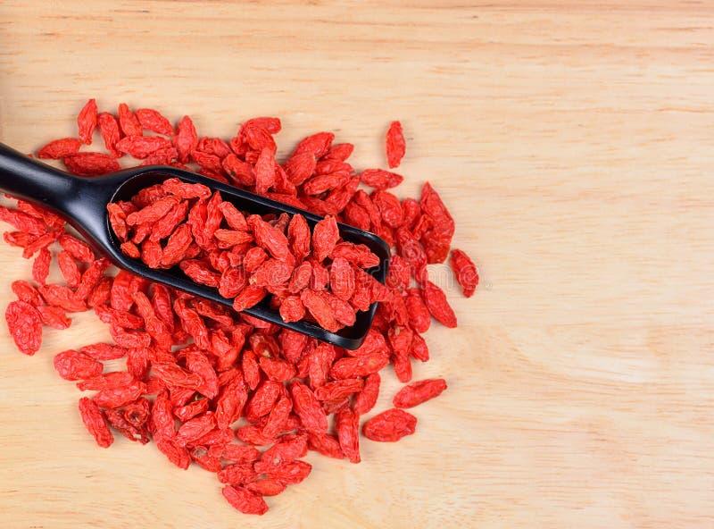 Bagas secadas vermelho do goji na colher de madeira foto de stock
