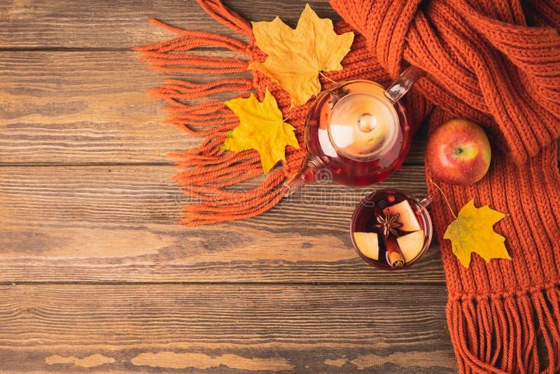 Bagas vermelhas da maçã do outono da bebida em um copo de vidro um bule e um lenço alaranjado em um fundo de madeira Ch? quente d fotografia de stock