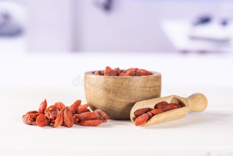 Bagas vermelhas secadas do goji com cozinha branca atrás foto de stock royalty free