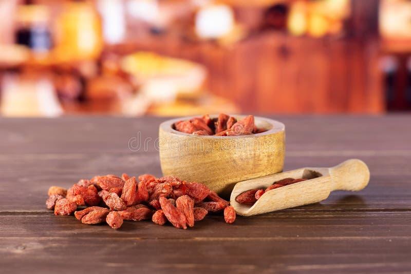 Bagas vermelhas secadas do goji com cozinha rústica imagem de stock royalty free