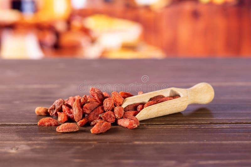 Bagas vermelhas secadas do goji com cozinha rústica fotografia de stock royalty free
