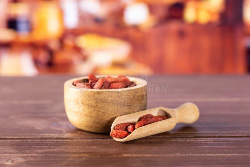 Bagas vermelhas secadas do goji com cozinha rústica fotografia de stock