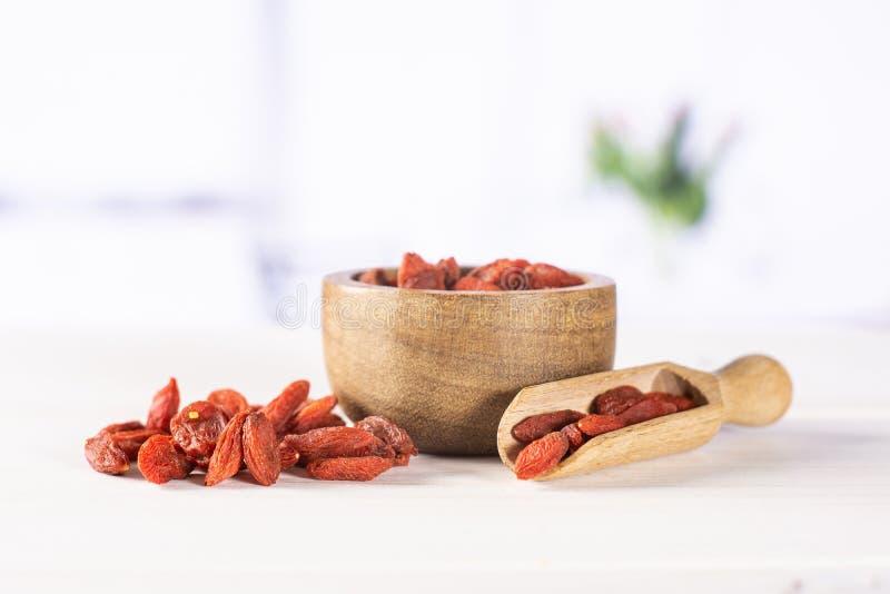 Bagas vermelhas secadas do goji com tulipas vermelhas fotografia de stock royalty free