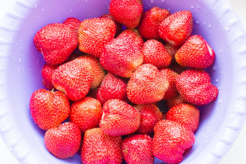 Bagas vermelhas suculentas frescas das morangos com gotas da água em um fim da placa imagens de stock