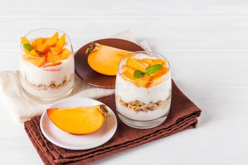 Bagatelle crémeuse de kaki en beaux verres, tranches mûres fraîches de fruit sur le fond en bois blanc Nourriture végétarienne sa images libres de droits