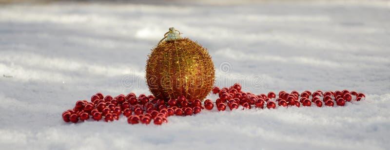 Bagattella dorata di Natale e perle rosse su neve immagini stock libere da diritti
