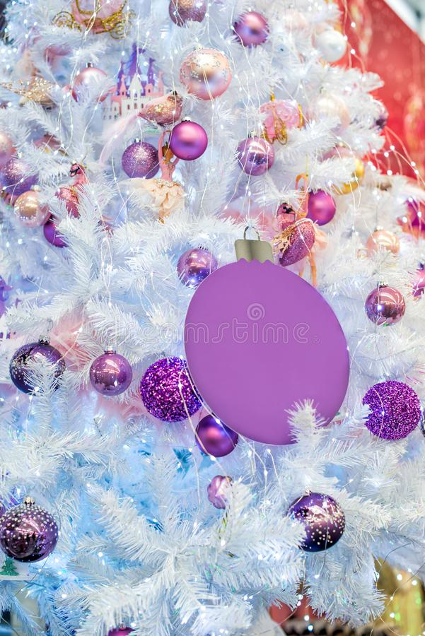 Bagattelle colorate porpora e ultraviolette d'avanguardia sull'albero di Natale artificiale bianco d'argento Fine in su Fuoco sel fotografia stock