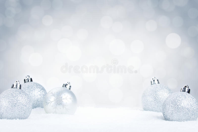 Bagattelle d'argento di Natale su neve con un fondo d'argento fotografia stock