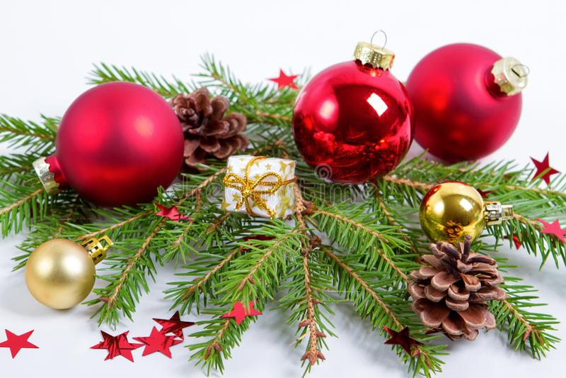 Bagattelle della decorazione di Natale con i rami dell'albero di abete su fondo bianco fotografie stock