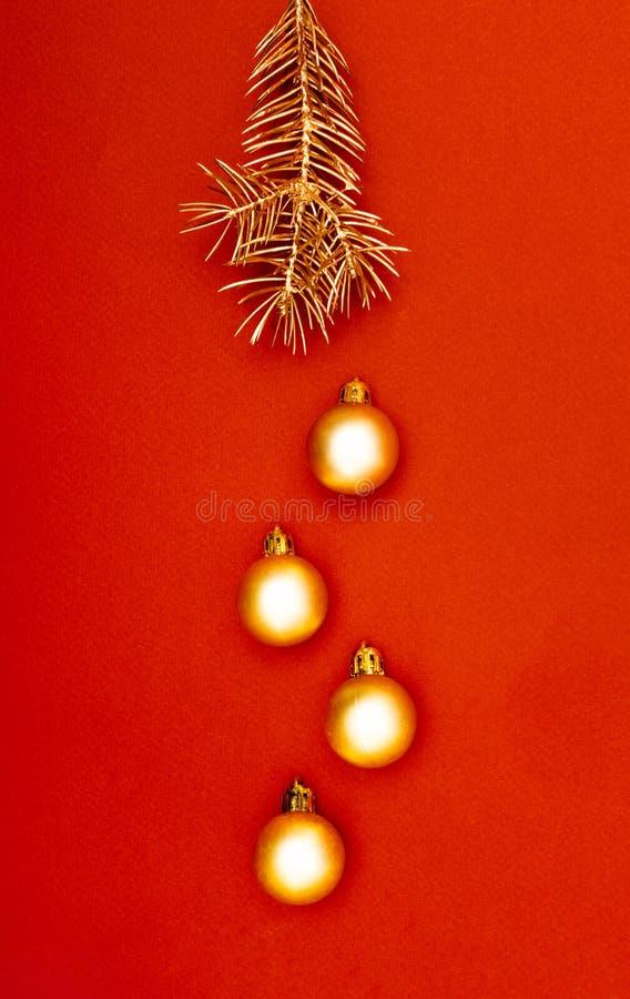 Bagattelle multiple dell'oro di Natale e singolo modello creativo della decorazione del ramo di pino sui precedenti rossi immagini stock libere da diritti