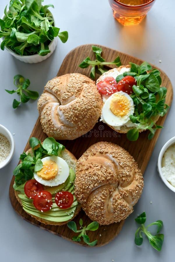 Bagel σάντουιτς με το τυρί κρέμας, το αβοκάντο, τις ντομάτες, το αυγό και τα πράσινα στο γκρίζο ξύλινο υπόβαθρο Εκλεκτική εστίαση στοκ εικόνα με δικαίωμα ελεύθερης χρήσης