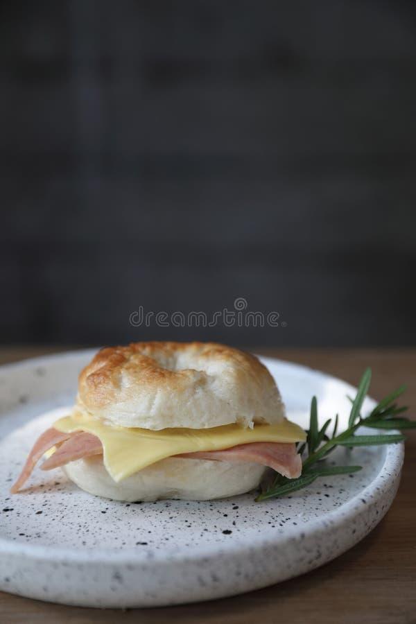 Bagel τυρί ζαμπόν στενό σε επάνω σε ένα πιάτο στη καφετερία στοκ εικόνα με δικαίωμα ελεύθερης χρήσης