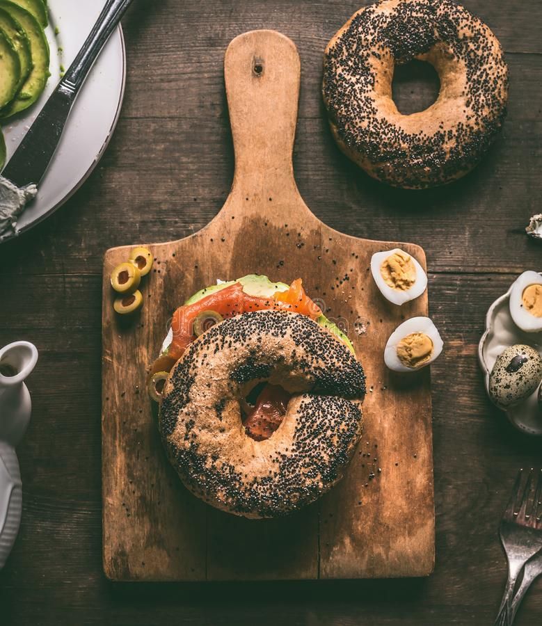Bagel bread on cutting board topped with salmon, avocado, cooked quail eggs and fresh cheese royalty free stock photos