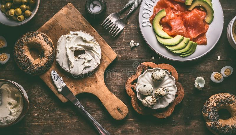 Bagel bun spread with cream-cheese on rustic breakfast table with ingredients: salmon, avocado, hummus and quail eggs stock photography