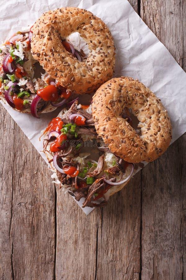 Bagel con carne di maiale e salsa tirate sulla tavola la cima verticale rivaleggia fotografia stock libera da diritti