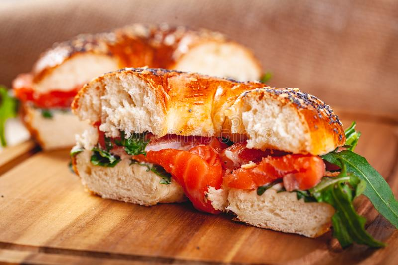 Bagel with cream cheese, smoked salmon and arugula salad cut in half on wooden board. stock image