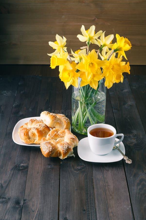 Bagel crostosi di recente al forno del sesamo con la tazza di tè immagini stock