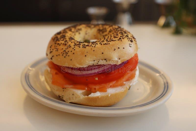 Bagel de style de New York avec les saumons fumés avec le fromage fondu, la tomate, l'oignon et les câpres images stock