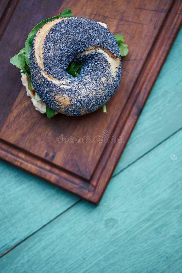 Bagel delicioso da semente de papoila em uma tabela rústica de turquesa imagem de stock