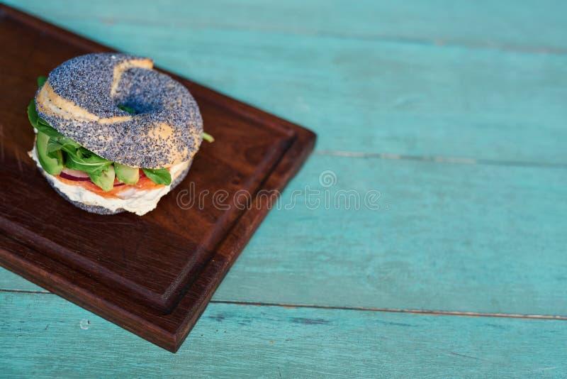 Bagel do queijo creme e dos salmões em uma tabela rústica de turquesa fotos de stock royalty free