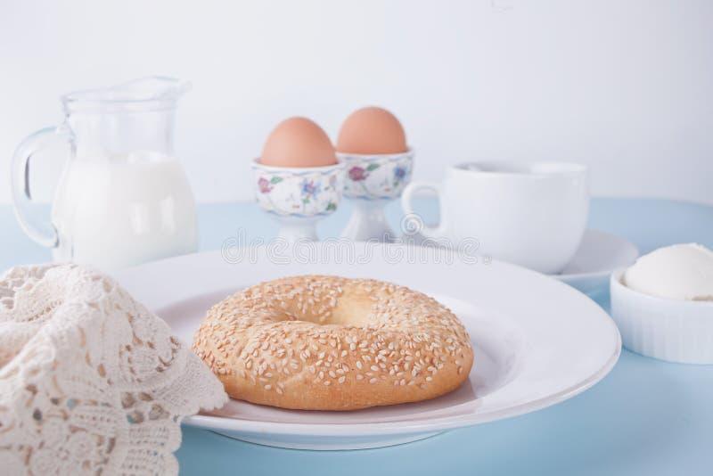 Bagel fresco su un piatto bianco con il formaggio cremoso, del tazza di caffè e le uova per la prima colazione fotografia stock