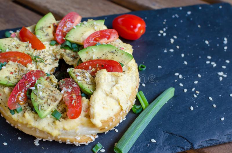 Bagel with hummus, avocado slices, spices, green onion, tomatoes cherry and sesame seeds on the black stone desk. Close up stock photos