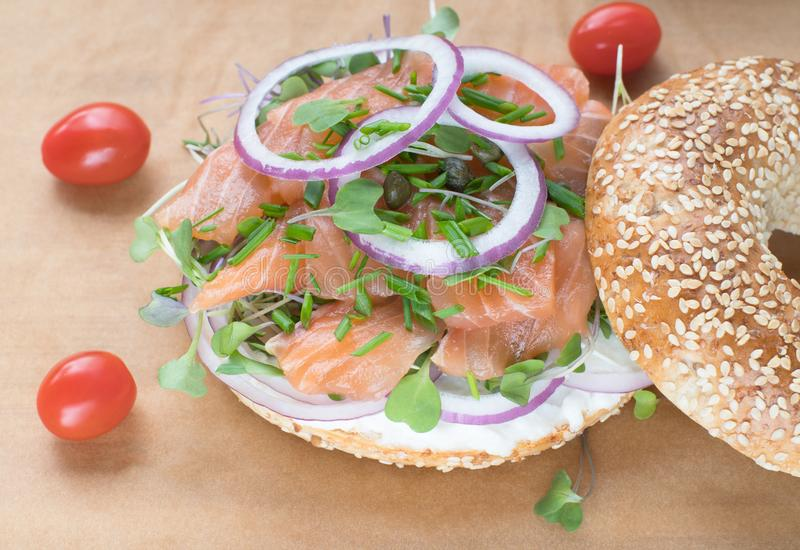 Bagel sandwich with creame cheese, salmon,onion,tomato,greens,chives close-up on a wooden background. Delicious bagel, golden stock images