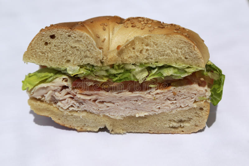 Bagel sandwich with turkey breast, lettuce and tomato royalty free stock image