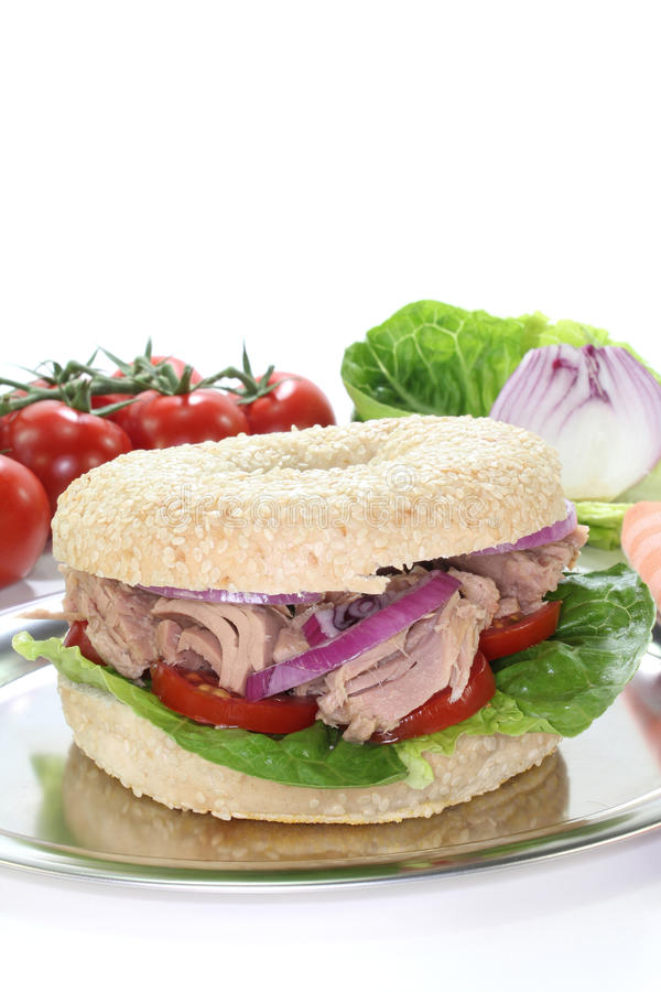 Bagel with tuna. Tomatoes, onions, and lettuce on white background stock images