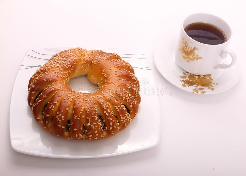 Tea with bagel. Bagel on white dish with cup of tea over white background stock image