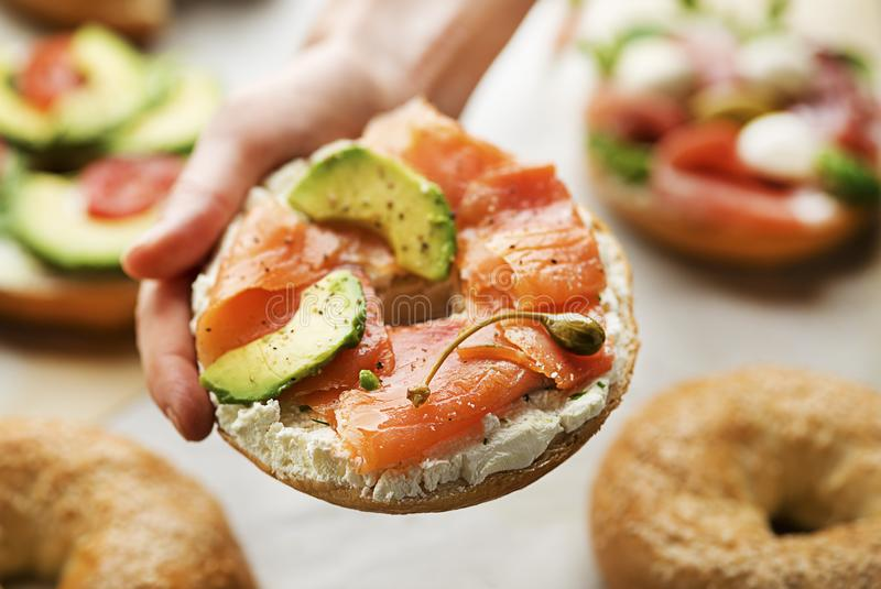 Holding Healthy Bagel with smoked salmon and avocado royalty free stock photography