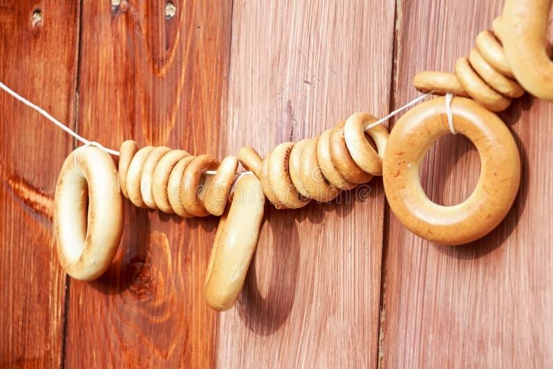 Bagelhängning på rep på träbakgrund royaltyfria bilder