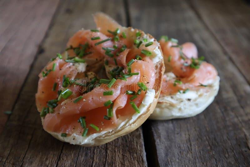 Bagels avec le fromage de saumon et fondu fumé sur le conseil en bois images libres de droits