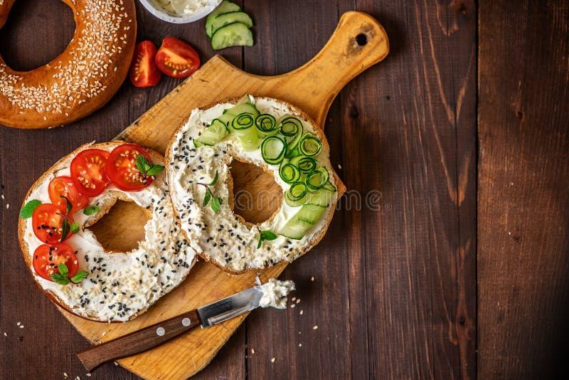 Bagels com queijo creme, sésamo, tomate e pepino em uma placa de madeira Configuração do plano da vista superior Com espaço da có imagens de stock
