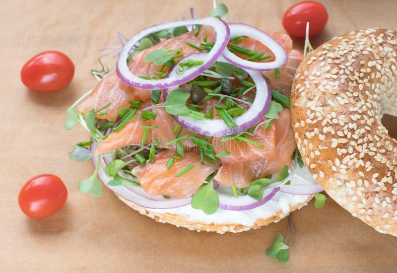 Bagelsmörgås med creameost, lax, lök, tomat, gräsplaner, ch arkivbilder
