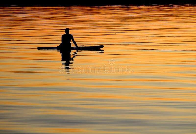 Silhouetted paddle boarder peaceful sunset stock photo