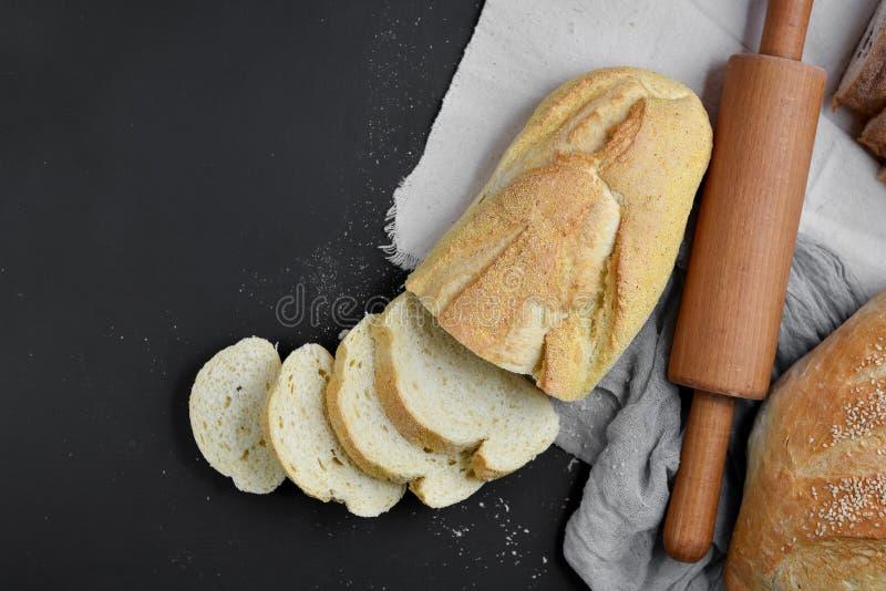 Bageri - guld- lantliga vresiga loaves av bröd och kavlen på svart svart tavlabakgrund Lekmanna- lägenhet, bästa sikt royaltyfri foto